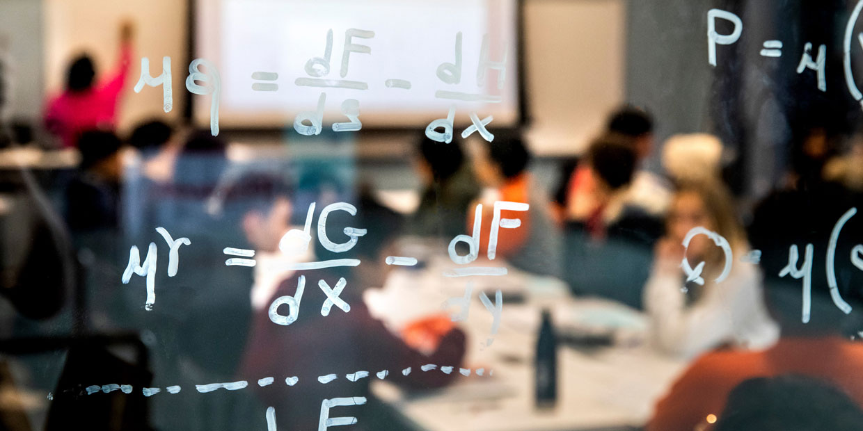 blurred view of an engineering lecture in the background with equations written on window in foreground
