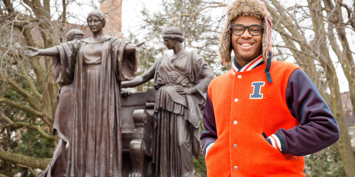 student posing with the Alma Mater statue
