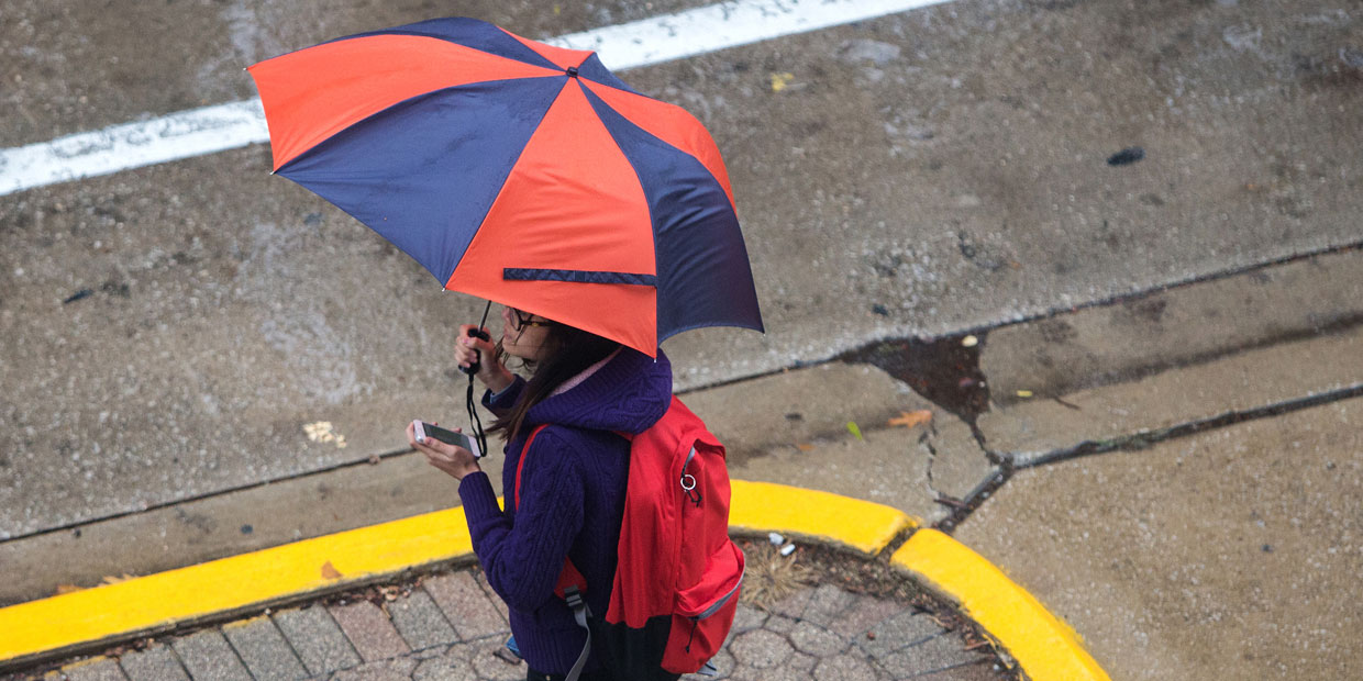 student holding an umbrella while waiting for the bus