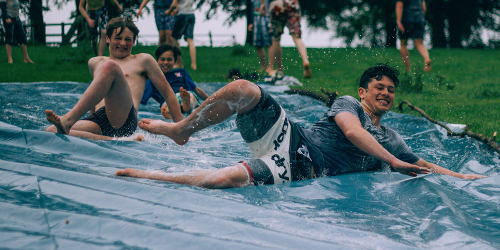 students sliding in water