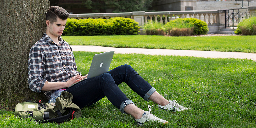 Student using laptop on the quad.