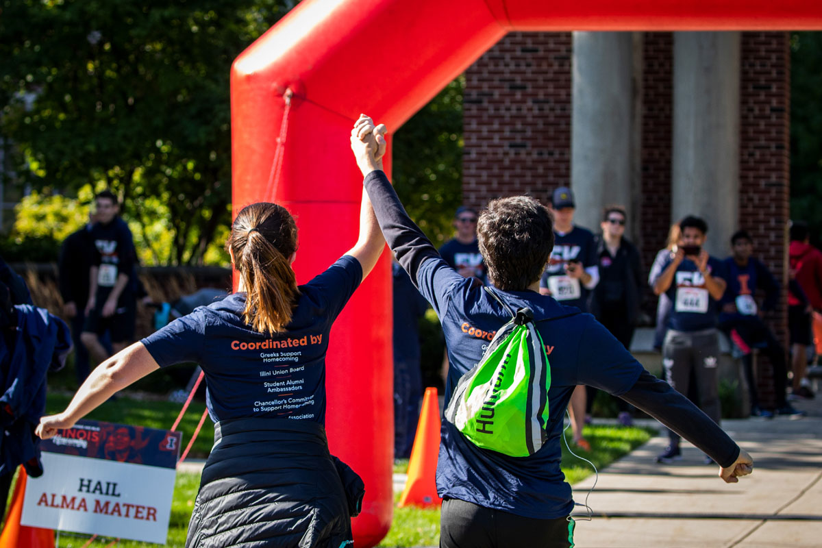 friends holding hands while crossing the finish line at Illinois' Homecoming 5K