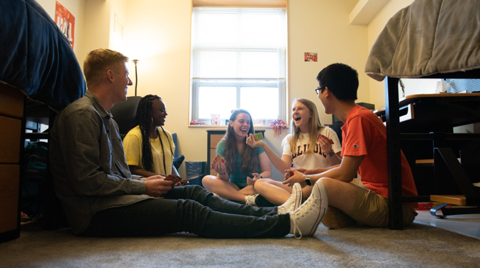 students laughing and playing a game together in their dorm room