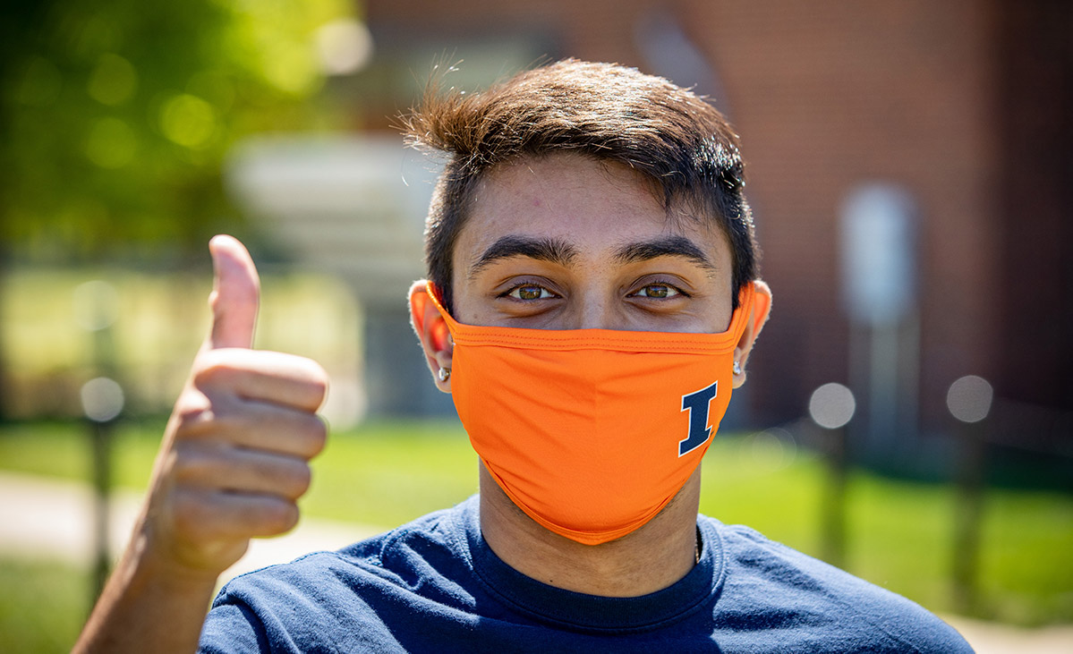 student wearing an orange & blue Illinois mask giving a thumbs up