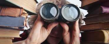 student peering through binoculars