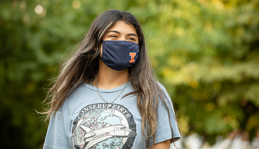 female student posing with a UIUC branded face covering