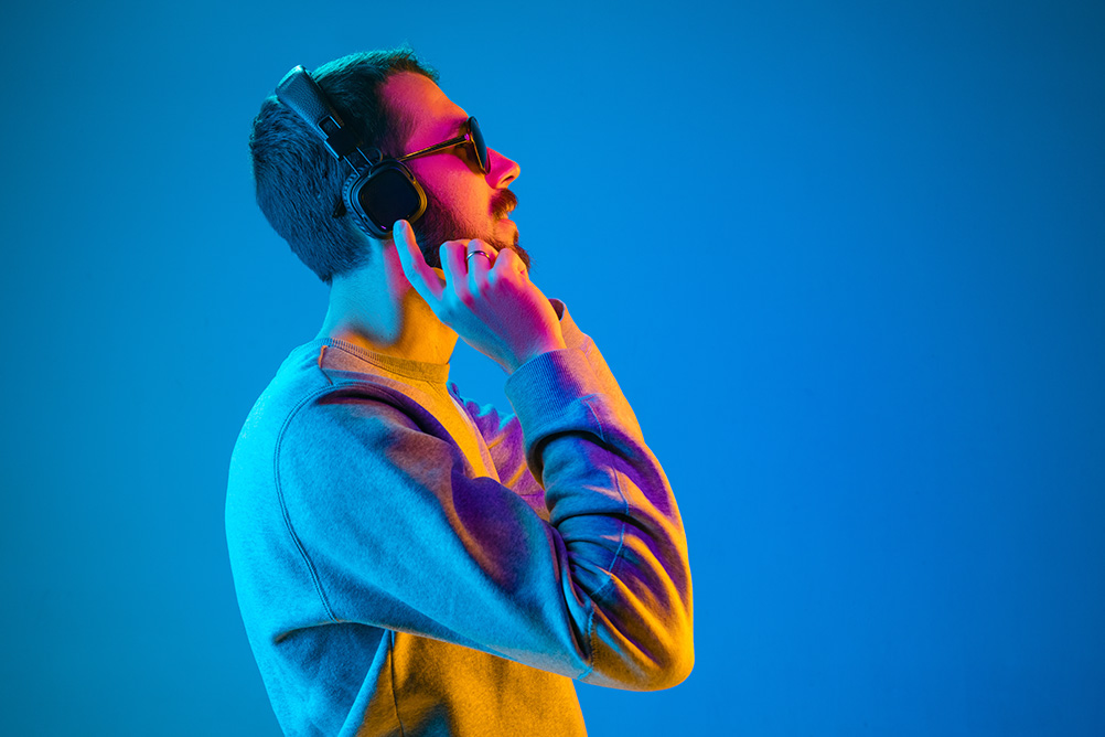 young man listening to music covered with orange and blue light